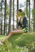 Runner resting eating apple on mossy rock in woods Stock Photos