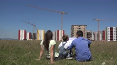 Young family sitting on green grass and looking at construction project, block Stock Footage