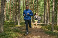 Runners running on trail in woods Stock Photos