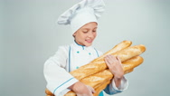 Close up portrait young baker girl child holds bread baguettes and smiling Stock Footage