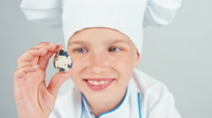 Close up portrait girl holds quail egg in her hand and smiling at camera Stock Footage