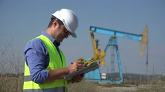 Young worker take notes close a oil pump, engineer writting Stock Footage