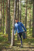 Runner stretching leg at tree in woods Stock Photos