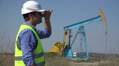 Young engineer searching around, worker close a oil pump Stock Footage
