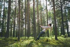 Runner using resistance band on tree in woods Stock Photos