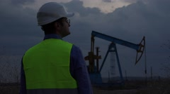 Young engineer talking at the phone close oil pump, evening sky Stock Footage