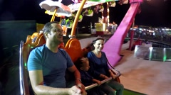 Family have fun in a rotating wheel at amusement park, night Stock Footage