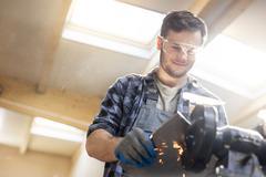 Smiling metal worker using sander in workshop Stock Photos