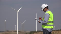 Engineer near windmills turbines writing down the technical parameters Stock Footage