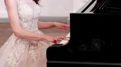 Girl playing the piano, concert, beautiful, slim figure of a young woman dressed Stock Footage