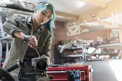 Young female mechanic with blue hair repairing part in auto repair shop Stock Photos