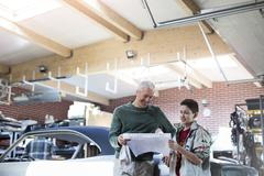 Father and son reviewing plans in auto repair shop Stock Photos