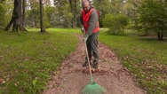 Man with rake collect leaves on path in park Stock Footage