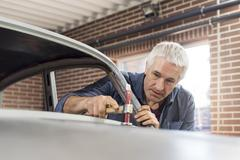 Focused mechanic using hammer on automobile hood in auto repair shop Stock Photos