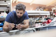 Focused mechanic examining car parts in auto repair shop Stock Photos