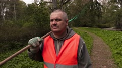 Man with rake walking in the park Stock Footage