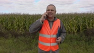 Farmer with folder using smart phone on corn field Stock Footage