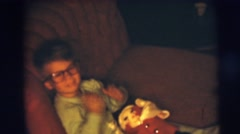 1967: young boy with glasses on sofa on christmas CAMDEN, NEW JERSEY Stock Footage