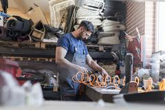 Mechanic using equipment at workbench in auto repair shop Stock Photos