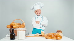 Cute baker girl standing near kitchen table with bakery products isolated on Stock Footage