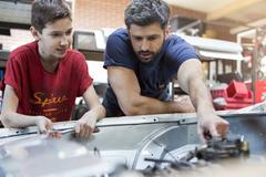 Father and son fixing car engine Stock Photos