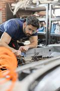 Focused mechanic fixing car in auto repair shop Stock Photos