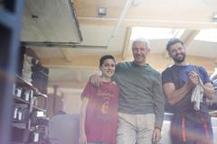 Portrait smiling family mechanics in auto repair shop Stock Photos