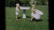 1967: two children playing with a hose and a basin in the garden CAMDEN Stock Footage