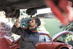 Mechanic underneath car fixing brakes Stock Photos
