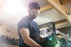 Steel worker using sander in workshop Stock Photos