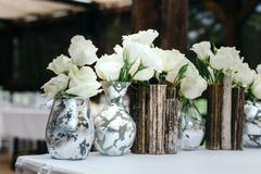Beautiful decor at the wedding. Arrangement of white flowers, in vases reeds. On Stock Photos
