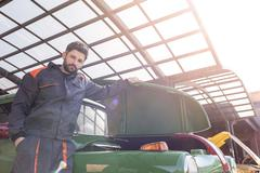 Portrait confident mechanic fixing classic car in auto repair shop Stock Photos