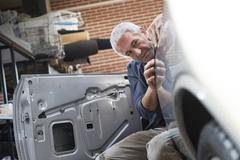 Focused auto body worker examining panel on car Stock Photos