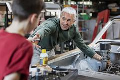 Father and son rebuilding classic car engine in auto repair shop Stock Photos