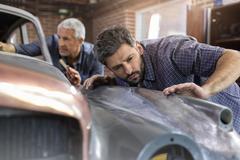Focused mechanic examining classic car panel in auto repair shop Stock Photos