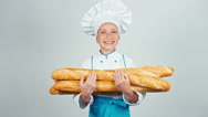 Portrait young baker girl child holds bread baguettes and smiling at camera Stock Footage