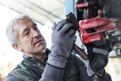 Close up focused mechanic replacing brake pads in auto repair shop Stock Photos