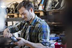 Mechanic fixing car part in auto repair shop Stock Photos
