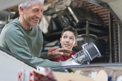 Smiling father and son fixing car engine in auto repair shop Stock Photos