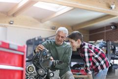 Father and son rebuilding engine in auto repair shop Stock Photos