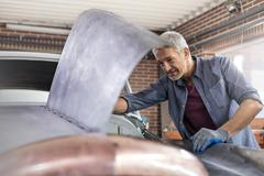 Mechanic looking under automobile hood in auto repair shop Stock Photos