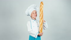 Baker girl 7-8 years child holds bread baguette and smiling at camera Stock Footage
