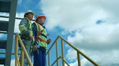 Workers in production plant as team discussing, industrial scene in background Stock Footage