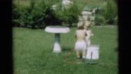 1967: little children in yard playing with garden hose outside CAMDEN Stock Footage