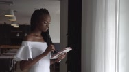 Portrait of a beautiful african female fashion model typing something on tablet Stock Footage