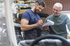 Mechanics with clipboard working in auto repair shop Stock Photos