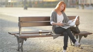 Smiling woman with red hair sitting on a bench with coffee and reading newspaper Stock Footage