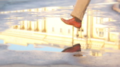 Man jumping happily in the puddle with beautiful reflection in sunny morning Stock Footage