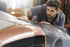 Focused mechanic examining classic car panel in auto repair shop Stock Photos