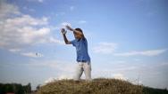 Boy jumping on haystack, enjoys having fun win, slow motion Stock Footage